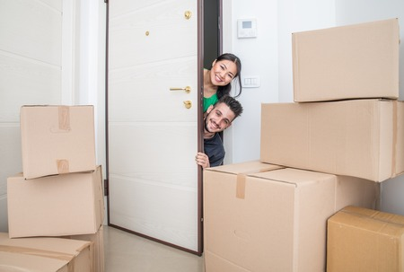 forniture: Happy couple with dog moving to a new home - Cheerful family starting a new life - Multi ethnic couple of lovers buy new apartment Stock Photo