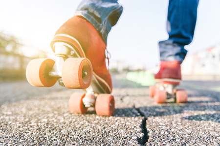 80s adult: Skater close up in action. Roller skates shoes with sun beam in the background.