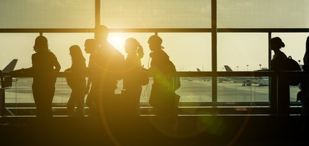 young  family: Silhouettes at the airport. Passengers on the sliding path with backlight