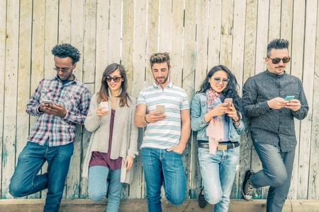 人: 年輕人低頭看著手機 - 青少年靠在牆上,並用他們的智能手機發短信 - 概念關於技術和全球通信