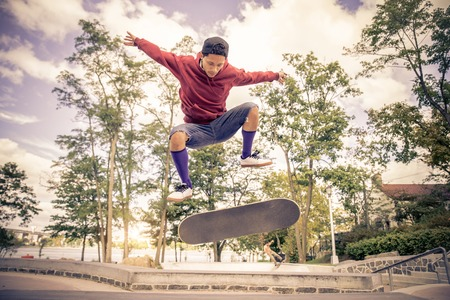 Skateboarder driving his board in a skate park - Young man doing a trick with his skate - Cool skater making a hollie with the skateboard Foto de archivo