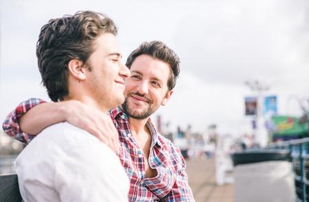 young sex: Гомосексуальная пара сидит в Санта-Монике пирса на скамейке. Счастливый портрет гей-пара