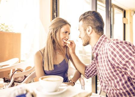 sexo pareja joven: Pareja tomando el desayuno en la mañana. hombre de alimentación a su chica con un trozo de croissant Foto de archivo