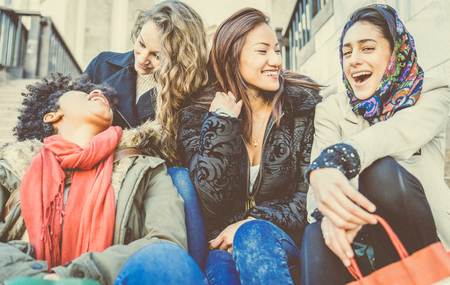 gorgeous woman: Group of attractive young women of different ethnics laughing and having party - Four students sitting outside university - Best friends spending time together Stock Photo