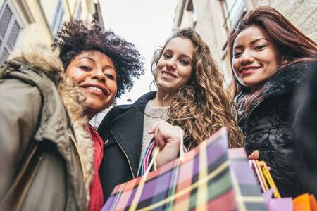 woman bag: Women with shopping bags - Portrait of three pretty girls walking and looking at shops - Tourists buying clothes and presents Stock Photo