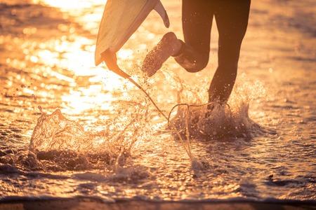 サーファーは彼のボードが付いている水で実行しています。偉大なサーフィンの日の準備