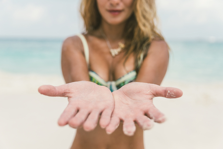 color healing: Woman on the beach with open hands showing palms. concept about vacations and tropical places Stock Photo