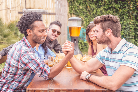 people partying: Group of mult-ethnic friends playing iron arm - Happy people partying and eating in home garden - Young active adults in a picnic area Stock Photo