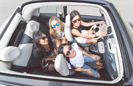 cars on road: Four girls having fun on a convertible car. People and transportation Stock Photo