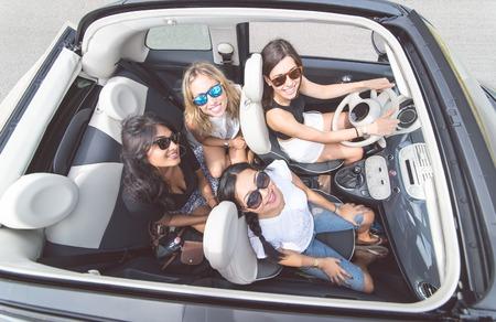 Quatro meninas que têm o divertimento em um carro conversível. Pessoas e transporte