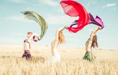 Buikdanseres groep in actie. Buikdanseres gilrs uitvoeren in een tarweveld. begrip over mode en discipline