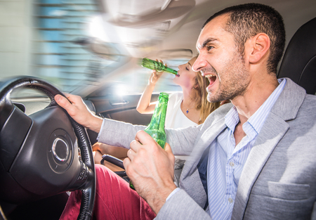 Couple driving drunk with the car. concept about bad behaviors on the street while driving Stock Photo