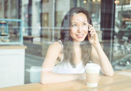 llamando: Hermosa llamada telefónica fabricación de la mujer dentro de una tienda