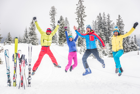 having fun in the snow: Group of skiers jumping and having fun