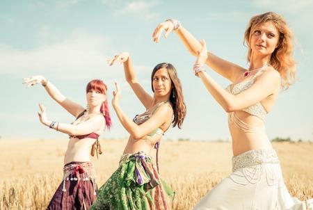 disciplina: Vientre grupo bailarín en acción. Gilrs bailarina del vientre actuando en un campo de trigo. concepto sobre la moda y la disciplina Foto de archivo