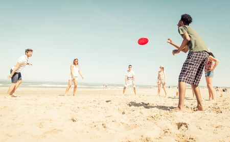 Group of friends playing with flying disc on the beach Stock Photo