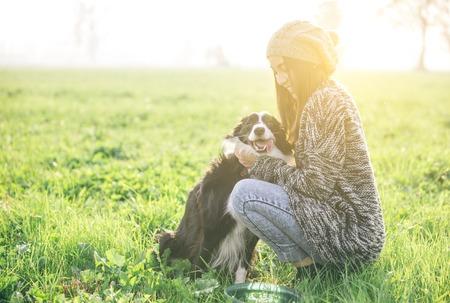 Молодая женщина, играя и наслаждаясь время со своей собакой