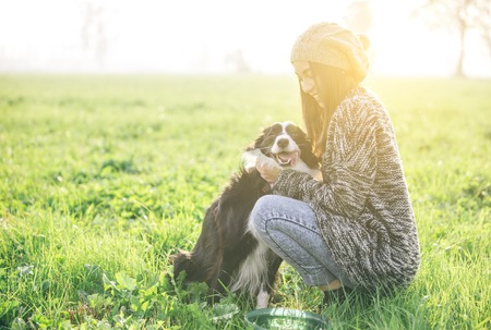 Junge Frau spielen und genießen die Zeit mit ihrem Hund Standard-Bild - 48357185