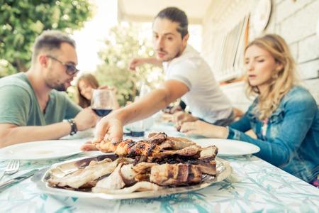 Groep vrienden die lunch in de tuin. Concept over barbecue met vrienden. focus op een bord met vlees