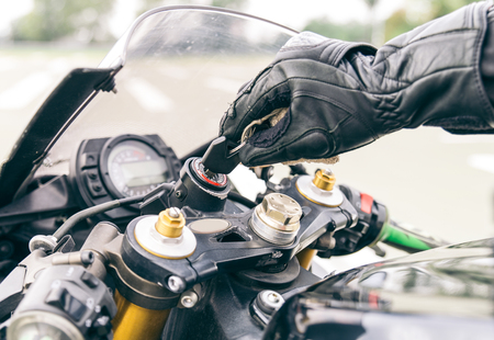 Motorcycle ignition action. Pilot inserting the key and starting the engine Archivio Fotografico