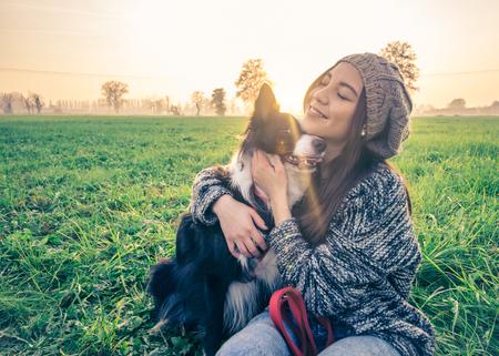 Giovane bella ragazza accarezza il suo cane in un parco al tramonto - donna asiatica che gioca con il suo cane Archivio Fotografico
