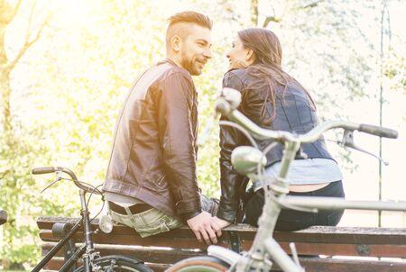 ライフスタイル: カップルが公園で自転車に乗るの後にリラックスしました。健康的なライフ スタイル、カップル、人々 の概念 写真素材