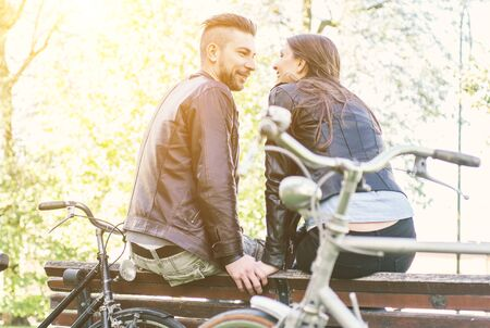 healthy lifestyle: Couple relaxing after a ride in the park with bicycles. Healthy lifestyle, couples and people concepts