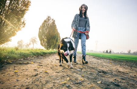 persona caminando: Joven hermosa chica caminando con su perro en un parque al atardecer - Mujer asi�tica que juega con su perro Foto de archivo