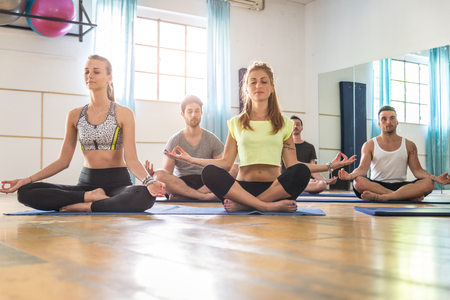 fitness gym: Group of sportive people doing yoga in a fitness gym - Sport group stretching after a work out Stock Photo