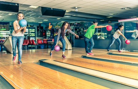 four people: Group of friends at bowling - Young people having fun at bowling, four players throwing balls on the bowling track