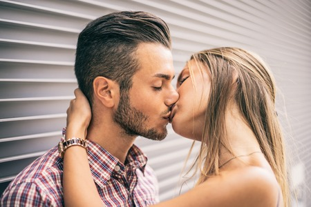 kissing lips: Couple of lovers kissing - Beautiful young woman hugging and giving a kiss on her handsome boyfriends lips Stock Photo