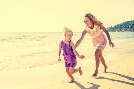 adult child: Mom and daughter running on the beach - Family moments, beautiful young mother trying to catch her daughter, having fun and enjoying summer holiday