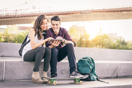 boy skater: Beautiful couple sitting on a bench outdoors and looking at tablet - Lovers having fun with new technology and shopping online
