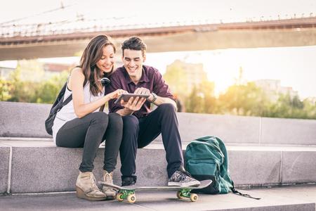 Bella coppia seduta su una panchina all'aperto e guardando tablet - Amanti divertirsi con le nuove tecnologie e lo shopping online Archivio Fotografico