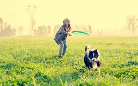 Молодая красивая девушка бросает fresbee своей собаке в парке на закате - азиатская женщина играет со своей собакой