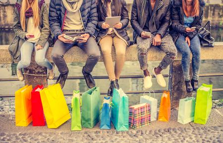 Grupa przyjaciół siedzi na zewnątrz z torby na zakupy - kilka osób posiadających smartfony i tablety - Pojęcia dotyczące stylu życia, zakupy, technologia i przyjaźni