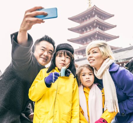 Happy multiethnic family taking a picture in front of Sensoji Temple in Tokyo. Stock Photo