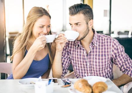 目でお互いを見てレストランでかなり愛好家の朝食を持っているコーヒー家で幸せなカップル