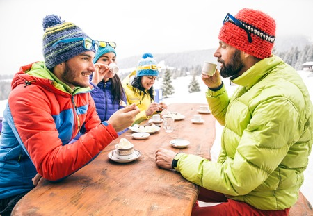 Group of mult-ethnic friends drinking hot chocolate and coffee - Happy people partying and eating in home garden - Young active adults in a restaurant on winter vacation
