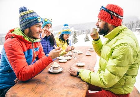 Grupo de amigos mult-étnico beber chocolate quente e café - As pessoas felizes festas e comer no jardim home - adultos ativos novos em um restaurante em férias de inverno