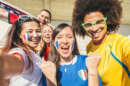 cheer: Group of sport supporters at stadium taking selfie - Fans of diverse nations screaming to support their teams - Multi-ethnic people having fun and celebrating on tribune at a sport event
