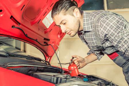 mecanico: Fijación del mecánico y comprobar un coche. Trabajar en el capó del coche Foto de archivo