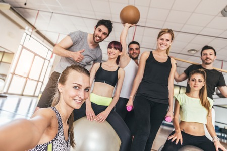 weight room: Group of sportive people in a gym taking selfie - Happy sporty friends in a weight room while training - Concepts about lifestyle and sport in a fitness club Stock Photo