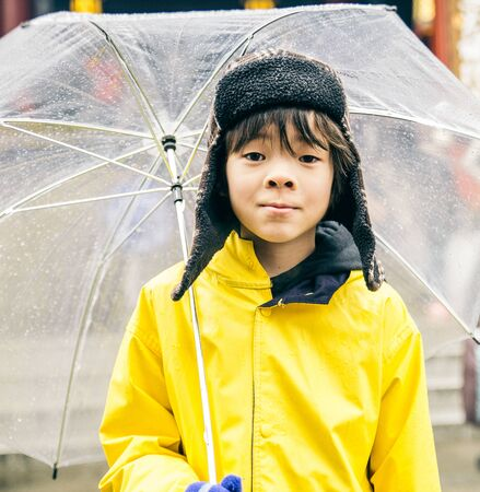winter weather: Asian young boy holding umbrella and going to school