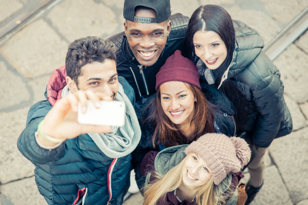 african student: Mixed race group of friends taking selfie in the city center