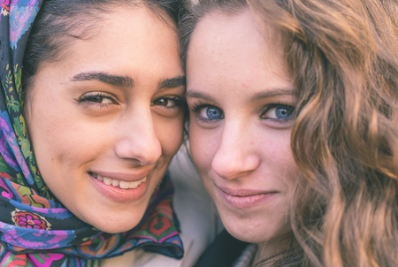 arab girl: Portrait with two girls from different ethnicity. Muslims and christians people perfectly integrated