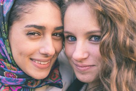 Portret met twee meisjes van verschillende etniciteit. Moslims en christenen mensen perfect geïntegreerd