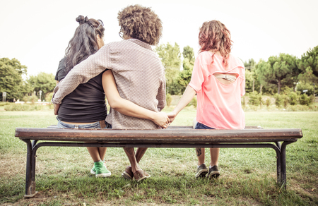 threesome: Woman cheating on her boyfriend with an other girl at the park. concept about relationships