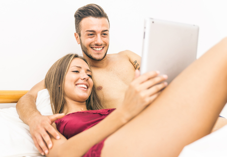 relaxing at home: Young couple watching something on the digital tablet, in bed. concept about couples and relationship Stock Photo