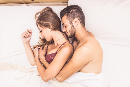 young wife: Happy couple in bed after waking up Stock Photo